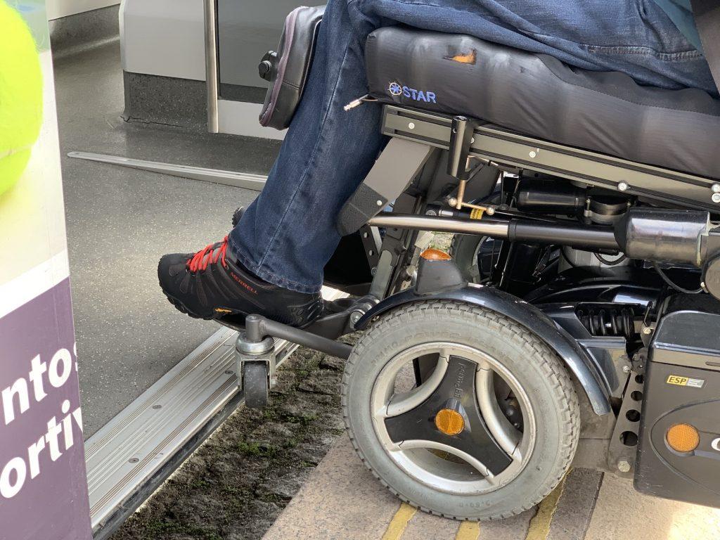 Pessoa em cadeira de rodas junto à porta de um eléctrico inacessível. Para recolha de informação visual