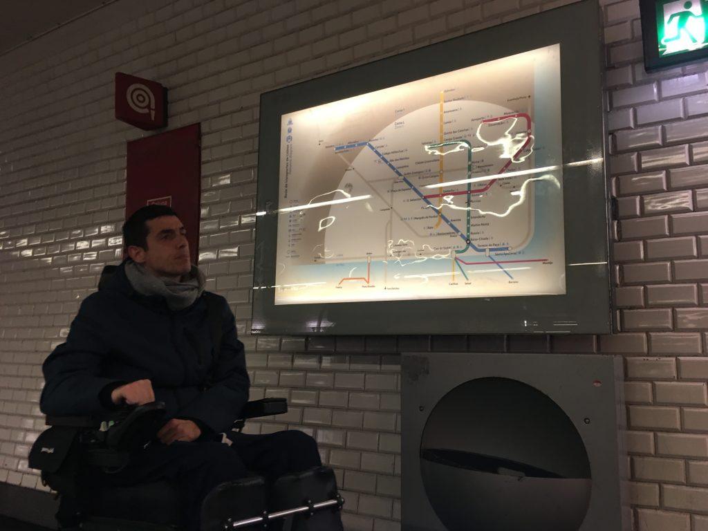 pessoa em cadeira de rodas a verificar um mapa do metro de Lisboa